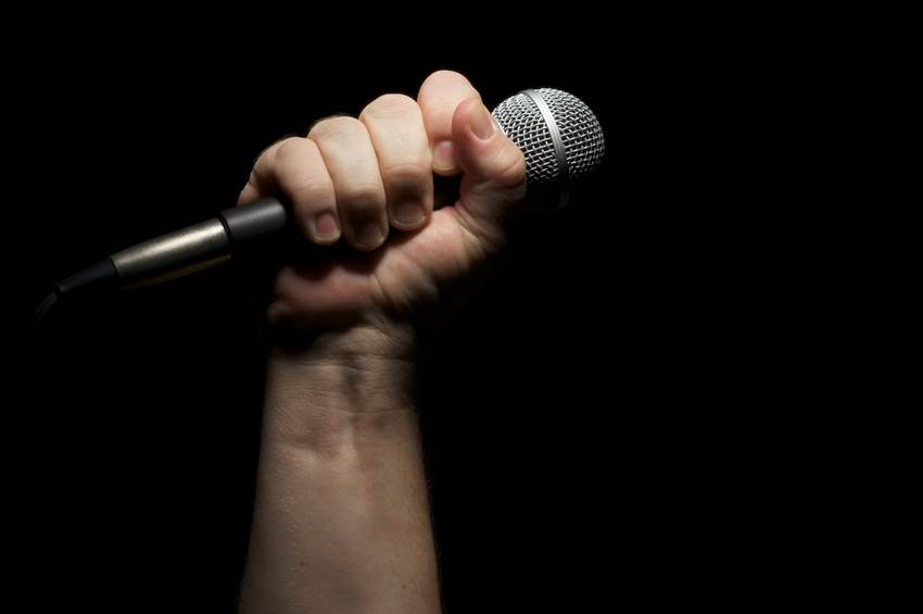 Microphone clinched firmly in male fist on a black background.